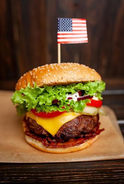 Smaczny świeży Domowy Burger Z Amerykańską Flagą Na Drewnianym Stole Premium Zdjęcia
