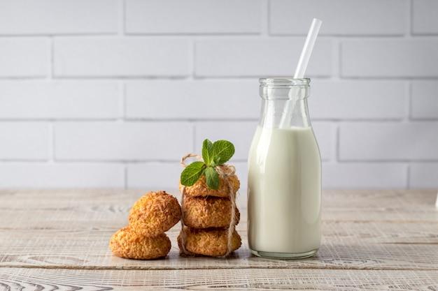 Smakowici Kokosowi Ciastka I Butelka Mleko Na Białym Drewnianym Stole Premium Zdjęcia
