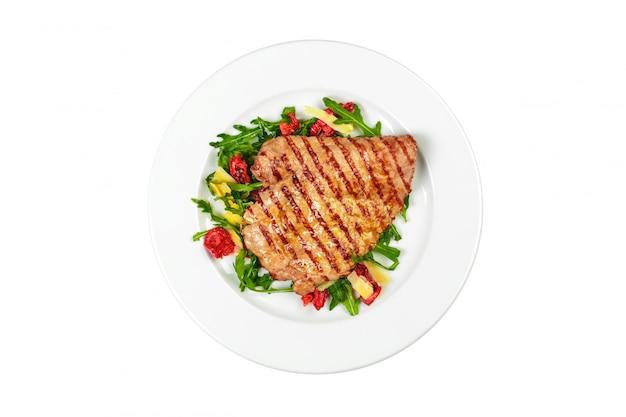 Smakowity wyśmienicie wieprzowina stek słuzyć z sałatką odizolowywającą na białym tle Premium Zdjęcia
