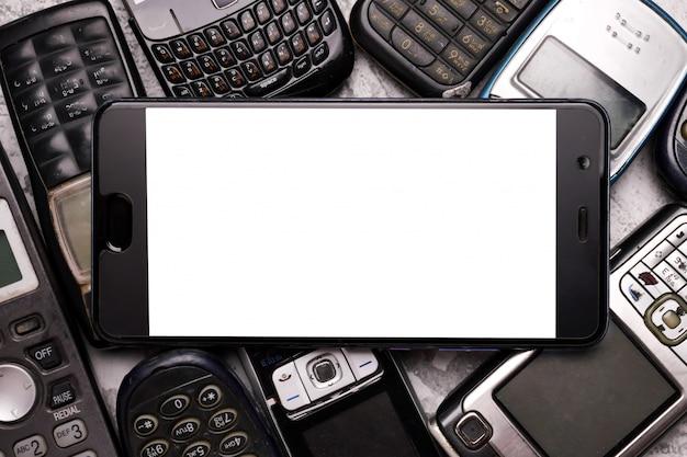 Smartfon Na Stosie Przestarzałych Telefonów Komórkowych. Premium Zdjęcia