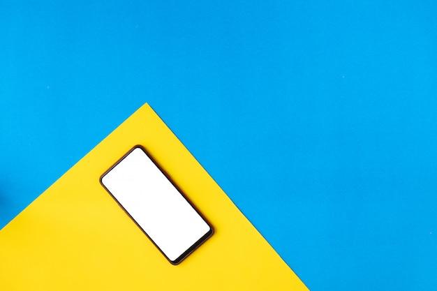 Smartfon Na żółtym Płaskim Leżał. Premium Zdjęcia