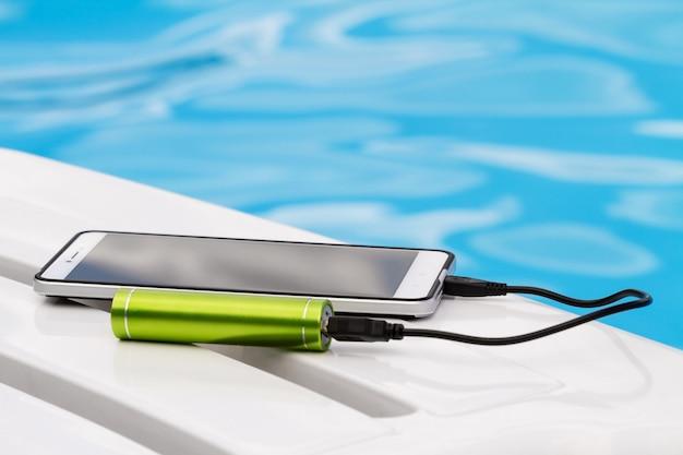 Smartphone podłączony do zielonej ładowarki przenośnej przez kabel usb na niebieskim tle wody. Premium Zdjęcia