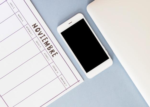 Smartphone w pobliżu kalendarza i papieru Darmowe Zdjęcia