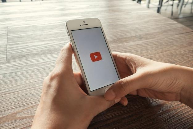 Smartphone Z Aplikacją Youtube Na Ekranie Leżącego Na Starym Drewnianym Biurku Darmowe Zdjęcia
