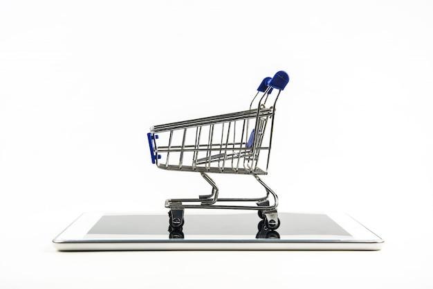 Smartphone z wózek na zakupy na białym tle Premium Zdjęcia