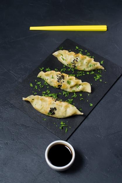 Smażący Japoński Gyoza Na Czarnej Kamień Desce, żółci Chopsticks. Premium Zdjęcia