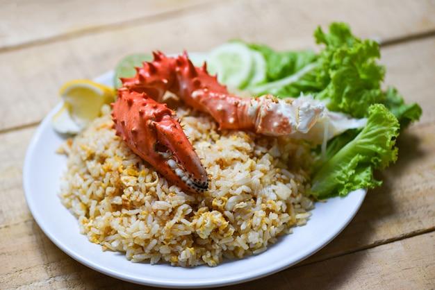 Smażona ryżowa kraba owoce morza jajko cytryna i ogórek na biały talerz drewniany stół - krab pazur Premium Zdjęcia