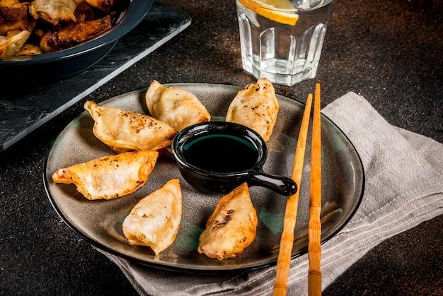 Smażone Azjatyckie Pierożki Gyoza Na Ciemnym Talerzu Podawane Z Pałeczkami I Sosem Sojowym Premium Zdjęcia