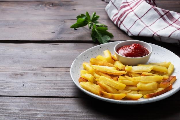 Smażone Frytki Ziemniaki Z Sosem Pomidorowym Ketchupem Na Talerzu. Premium Zdjęcia