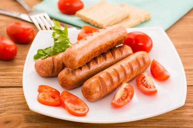 Smażone Kiełbaski I Pomidory Na Talerzu Premium Zdjęcia