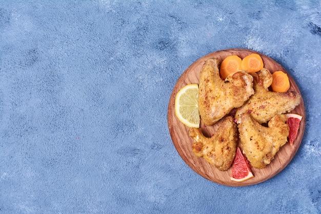 Smażone Skrzydełka Z Kurczaka Na Drewnianej Desce Na Niebiesko Darmowe Zdjęcia