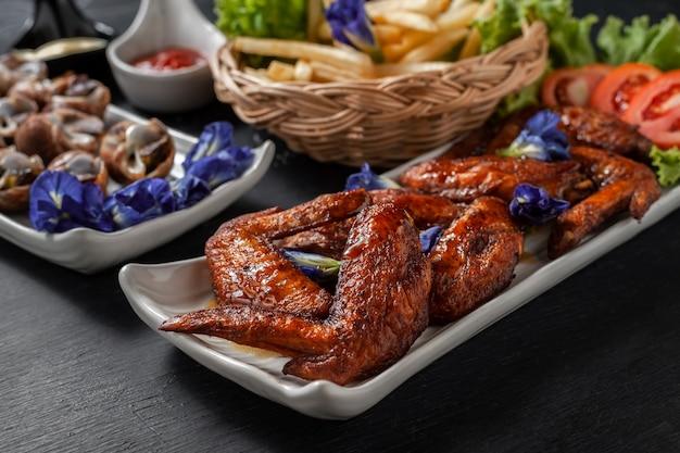Smażone Skrzydełka Z Kurczaka Ze Strumieniem Bryzonu I Frytkami Premium Zdjęcia