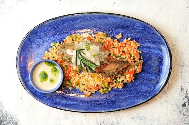 Smażone udko z kurczaka z bulgurem, warzywami i kremowym sosem Premium Zdjęcia