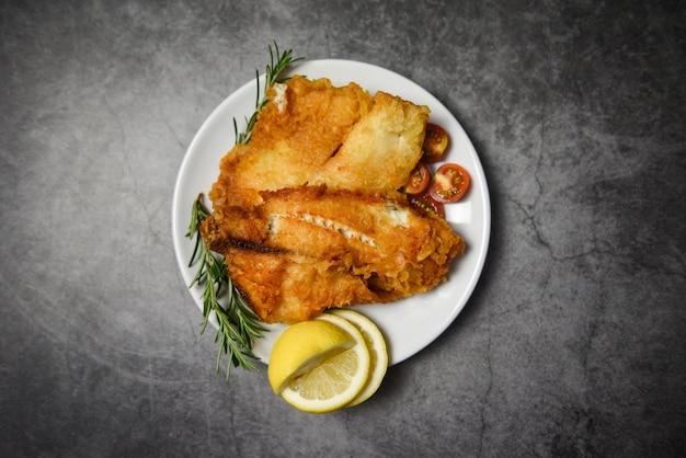 Smażony Filet Z Ryby Pokrojony Na Stek Lub Sałatkę Do Gotowania żywności Z Przyprawami Ziołowymi Rozmarynem I Cytryną - Filet Z Ryby Tilapia Chrupiący Podawany Na Białym Talerzu I Ciemnym Tle Premium Zdjęcia
