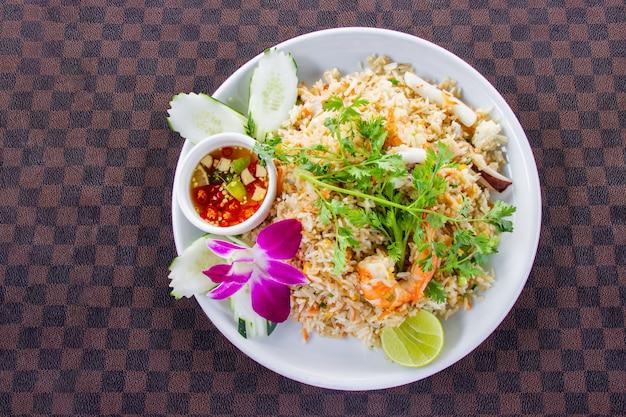 Smażony ryż z krewetkami na białym ceramicznym naczyniu ozdobionym orchideą Premium Zdjęcia