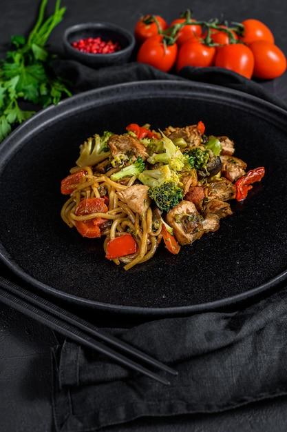 Smażyć Kurczaka Z Warzywami, Sosem Sojowym, Woka. Tradycyjne Azjatyckie Jedzenie. Kamienny Czarny Stół Premium Zdjęcia
