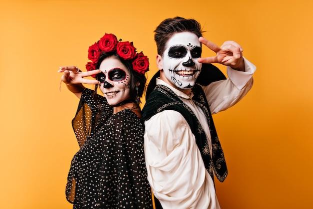 Śmiech Zombie Stojący Na żółtej ścianie. Urocza Para Z Meksykańskim Makijażem Chłodzi Na Imprezie Halloweenowej. Darmowe Zdjęcia