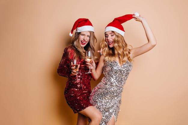 Śmiejąc Się Wesoła Kobieta W Czerwonej Sukience Tańczy Na Imprezie Noworocznej Z Przyjacielem Darmowe Zdjęcia