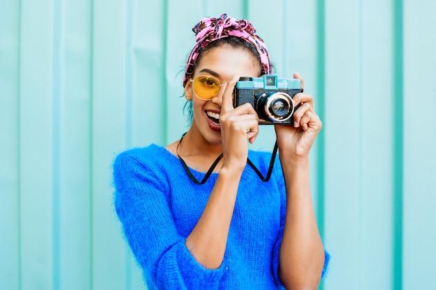 Śmiejąca Się Czarna Dziewczyna Z ładny Fryzury, Trzymając Aparat Retro I Patrząc Na Kamery. Darmowe Zdjęcia