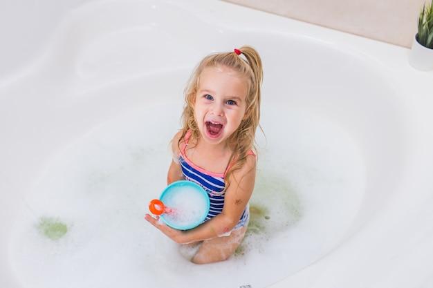Śmieszna Mała Dziewczynka Bierze Bąbla Skąpanie Premium Zdjęcia