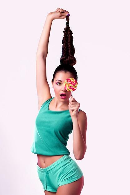 Śmieszna młoda kobieta w zielonym kombinezonu mienia lizaku i pozować Premium Zdjęcia
