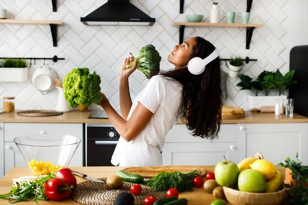 Śmieszna Mulatka W Dużych Bezprzewodowych Słuchawkach Tańczy Z Liśćmi Sałaty I Brokułami Na Nowoczesnej Kuchni Przy Stole Pełnym Warzyw I Owoców Darmowe Zdjęcia
