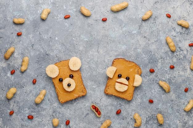 Śmieszna Niedźwiedzia I Małpy Twarzy Kanapka Z Masłem Orzechowym, Bananem I Czarną Porzeczką, Arachidy, Widok Z Góry Darmowe Zdjęcia