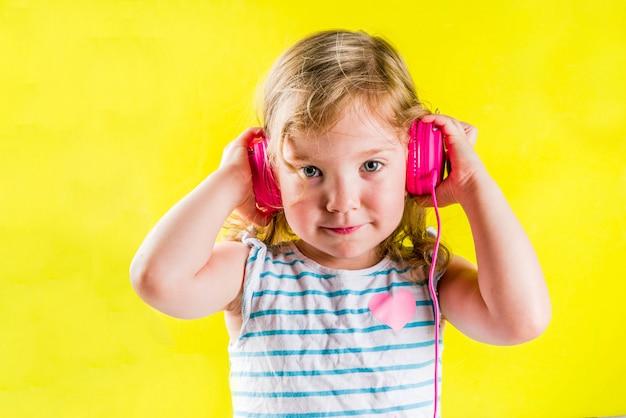 Śmieszna śliczna blondynka berbecia dziewczyna słucha muzykę z jaskrawymi różowymi słuchawkami Premium Zdjęcia