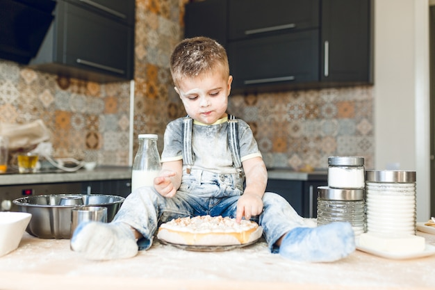 Śmieszne Dziecko Siedzi Na Stole W Kuchni Akustycznej, Bawi Się Mąką I Degustuje Ciasto. Darmowe Zdjęcia
