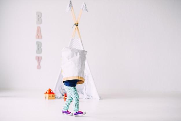 Śmieszne Małe Dziecko Biegające Po Jasnym Pokoju Z Papierową Torbą Na Głowie Na Dziecięcym Wigwamie Premium Zdjęcia