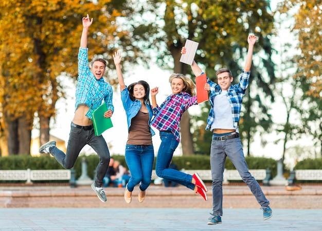 Śmieszni młodzi ucznie skaczą wpólnie w parku. Premium Zdjęcia