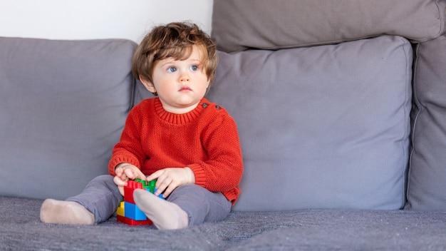 Śmieszny chłopiec siedzi na kanapie w czerwonym pulowerze Premium Zdjęcia