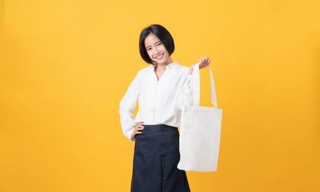 Smiley Azjatyckie Kobiety W Swobodnej Białej Koszulce I Trzymając Płótno Torba Na Logo Makiety Na żółtej ścianie Premium Zdjęcia