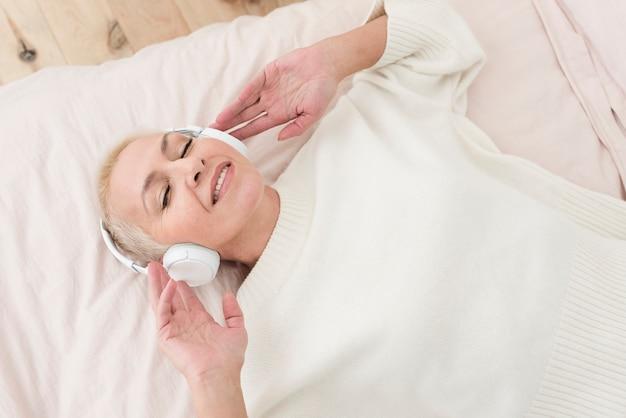 Smiley Dojrzała Kobieta Cieszy Się Muzykę Na Hełmofonach W łóżku Darmowe Zdjęcia