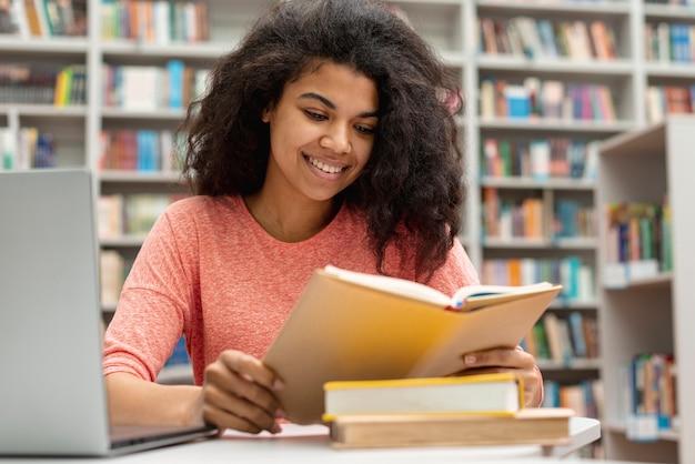 Smiley Dziewczyna Studiuje Laptop I Używa W Bibliotece Darmowe Zdjęcia