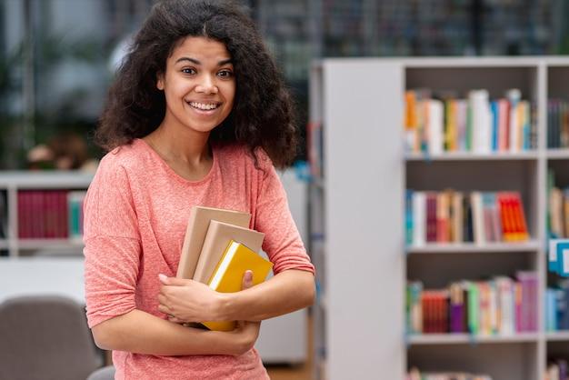 Smiley Dziewczyna W Bibliotece Na światowy Dzień Książki Darmowe Zdjęcia