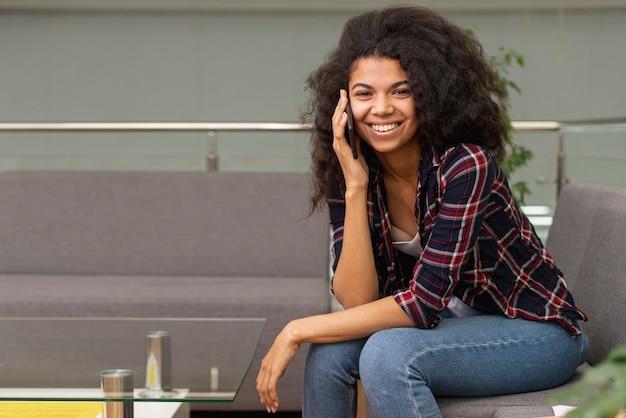 Smiley Dziewczyna W Bibliotece Rozmawia Przez Telefon Darmowe Zdjęcia