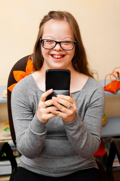 Smiley Dziewczyna Z Zespołem Downa Trzymając Telefon Darmowe Zdjęcia