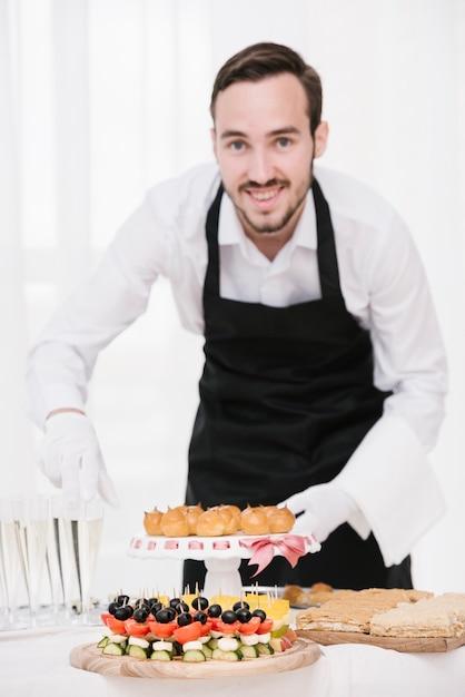 Smiley kelner z jedzeniem i napojami na stole Darmowe Zdjęcia