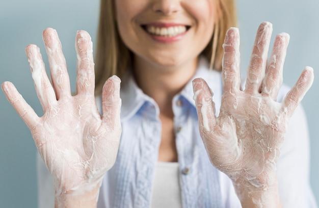 Smiley Kobieta Pokazuje Jej Ręki Z Mydłem I Pianą Darmowe Zdjęcia