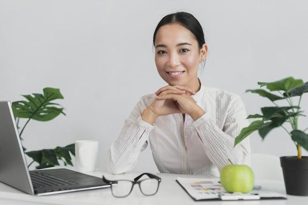 Smiley kobieta siedzi w biurze Darmowe Zdjęcia