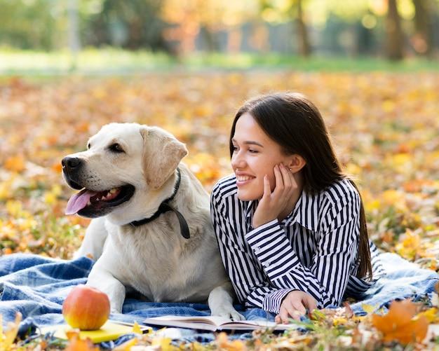 Smiley kobieta z psem w parku Darmowe Zdjęcia