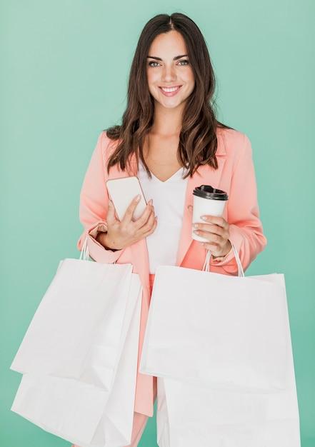 Smiley kobieta z sieci handlowych i smartphone Darmowe Zdjęcia