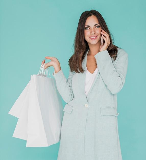 Smiley kobieta z torby na zakupy rozmawia przez telefon Darmowe Zdjęcia