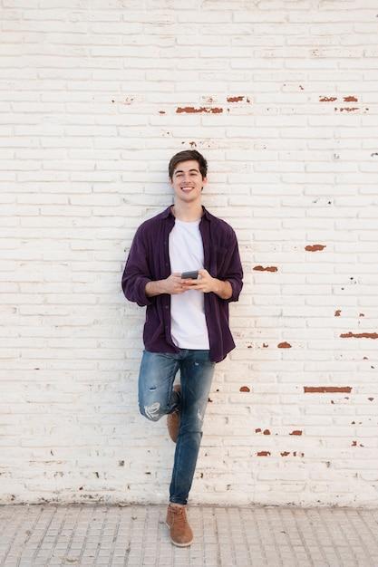 Smiley Mężczyzna Pozuje Podczas Gdy Trzymający Smartphone Darmowe Zdjęcia