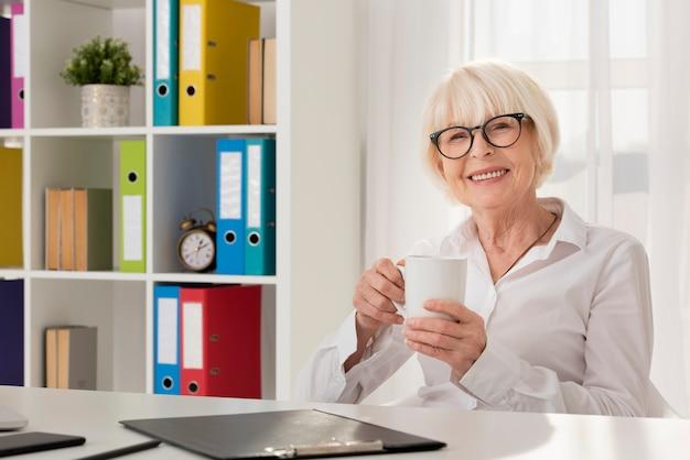 Smiley senior trzyma filiżankę w jej biurze Darmowe Zdjęcia