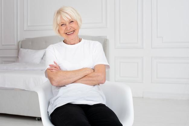 Smiley starsza kobieta siedzi na siedzeniu Darmowe Zdjęcia