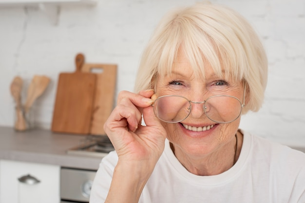 Smiley starsza kobieta trzyma eyeglasses Darmowe Zdjęcia