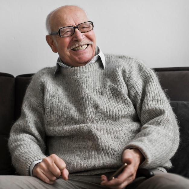 Smiley Starszy Mężczyzna W Domu Opieki, Trzymając Smartfon Darmowe Zdjęcia