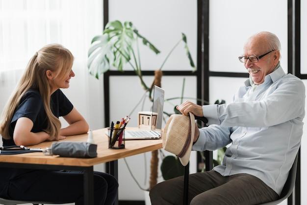 Smiley Starszy Mężczyzna W Domu Opieki Z Pielęgniarką Darmowe Zdjęcia
